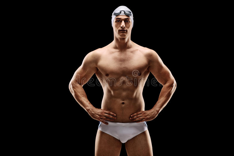 Handsome male swimmer in white swim trunks. Handsome young male swimmer posing in white swim trunks on black background royalty free stock image