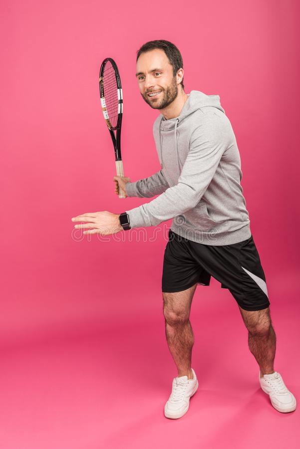 Handsome male tennis player with racket, isolated. On pink stock images