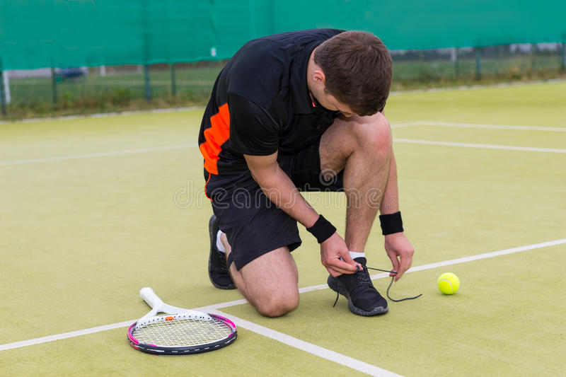 Handsome male tennis player tying shoelaces wearing a sportswear. Left racket and ball on a green grass court outdoor in summer or spring royalty free stock photography