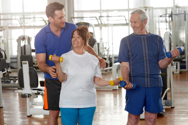Handsome male trainer instructing senior woman in gym. stock photo
