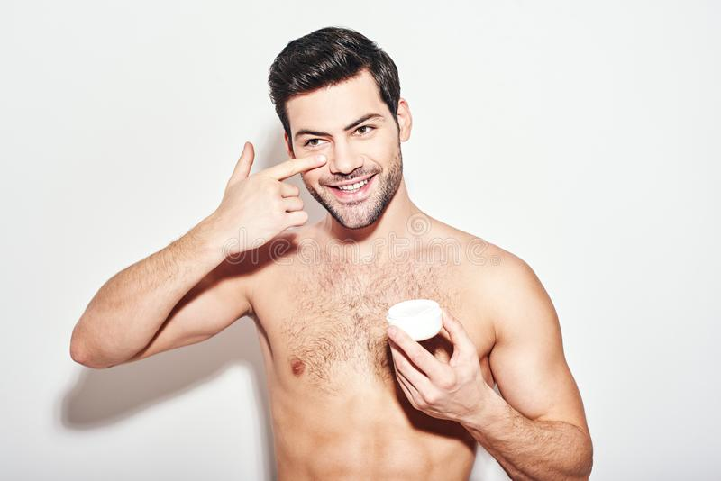 His skin needs good care. Handsome man applies eye cream standing isolated over white background stock photography