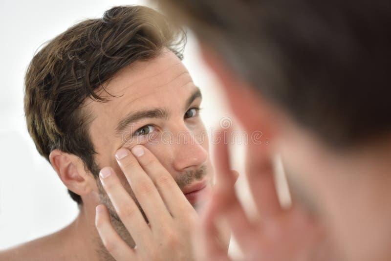 Handsome man applying facial cream stock images
