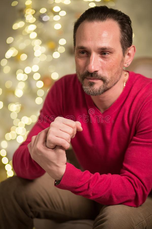 Handsome man in arm chair. Male adult with thoughtful look. Sitting in arm chair royalty free stock image