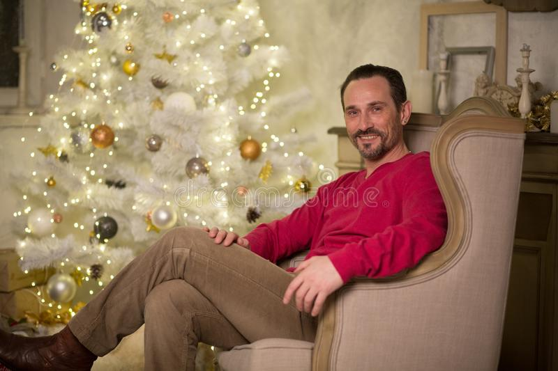 Handsome man in arm chair. Handsome men in red sweater sitting in arm chair. X-tree on background royalty free stock photography