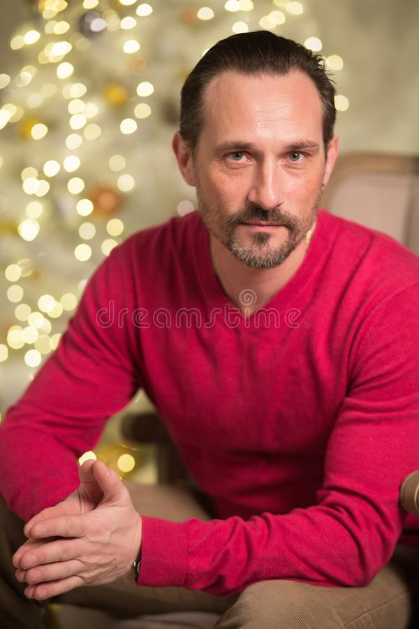 Handsome man in arm chair. Well-built male adult sitting in arm chair. Looking at camera royalty free stock image