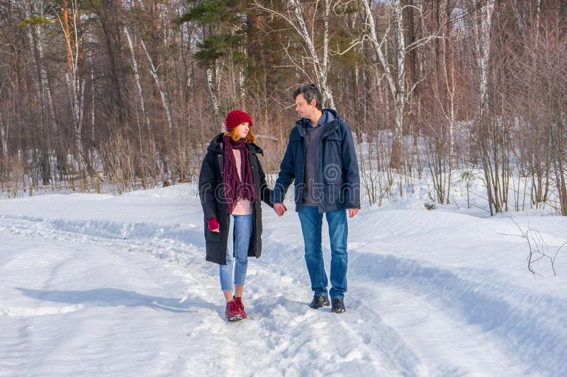 Handsome man and attractive young woman walking along snowy country road in sunny day. Beautiful look, male and female fashion,. Winter outfit. Winter holidays stock photos