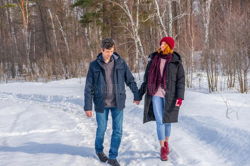 Handsome man and attractive young woman walking along snowy country road in sunny day. Beautiful look, male and female fashion,. Winter outfit. Winter holidays royalty free stock images