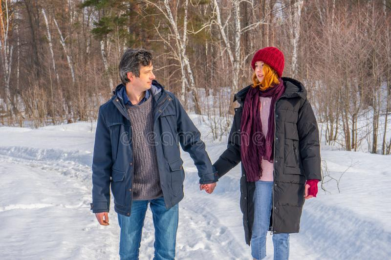 Handsome man and attractive young woman walking along snowy country road in sunny day. Beautiful look, male and female fashion,. Handsome men and attractive stock images