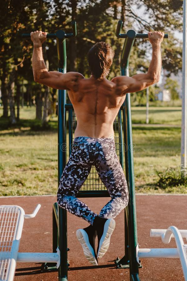 Man from the back doing pull ups outside royalty free stock image