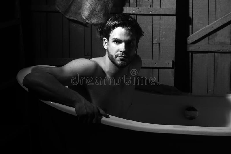 Handsome man in bath. One handsome serious sensual muscular young man with beautiful bare body sitting in white bath tub with foam taking shower looking forward stock photos