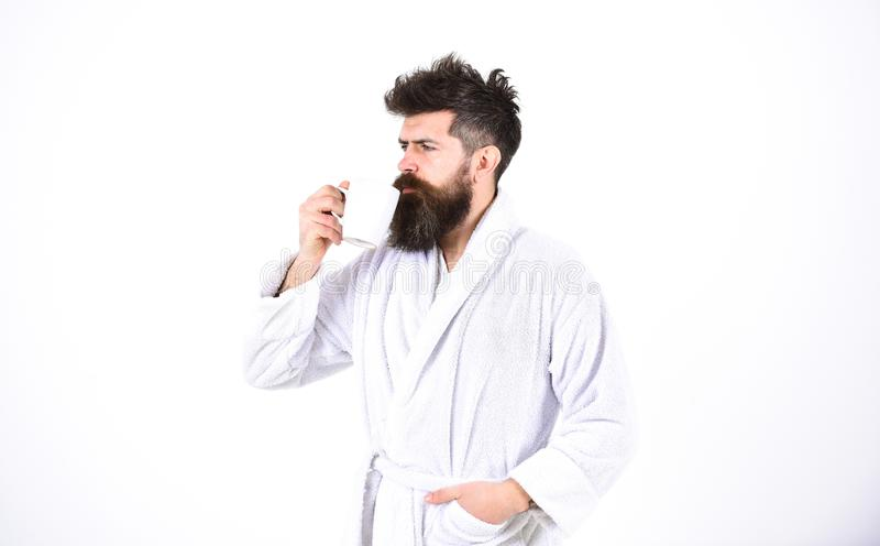 Handsome man in a bathrobe holding a cup on white background. Bearded guy drinking coffee or tea in the morning stock images