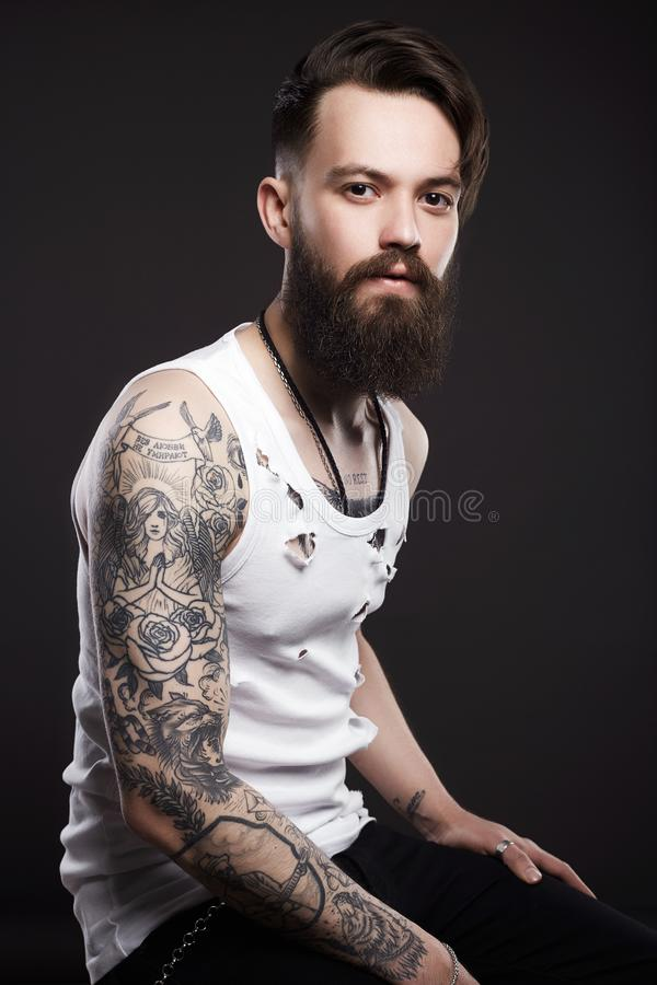 Handsome man with beard. Brutal boy with tattoo. Handsome man with beard. Brutal bearded hipster in vintage torn dirty shirt. Boy with stylish haircut and tattoo royalty free stock images
