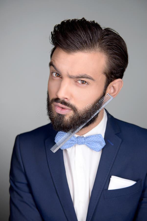 Handsome man with beard and comb in it. Photo of handsome stylish man with beard and comb in it. Man wearing classic dark blue suit and a blue bow tie. Man royalty free stock image