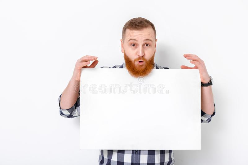 Man with beard holding big white card. stock photo