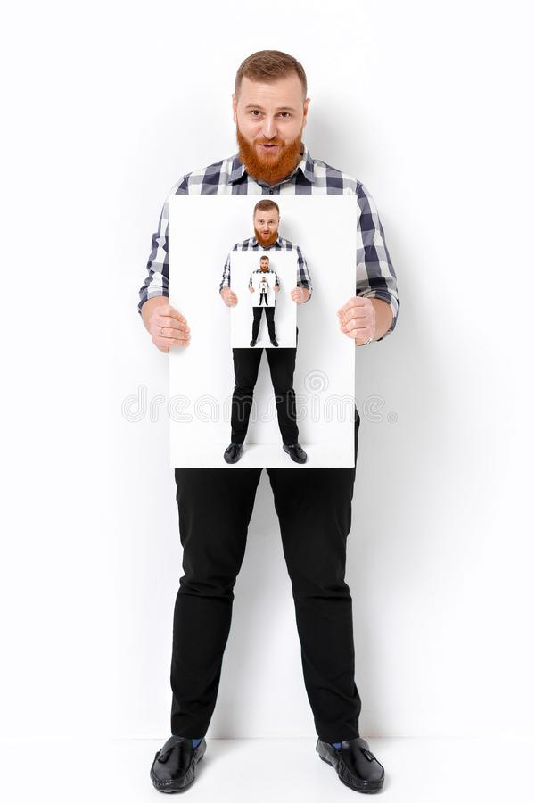 Man with beard holding big white card. stock photography