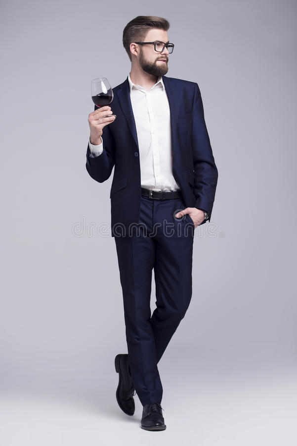 Handsome man with a beard holding a glass of wine in his hand stock photography