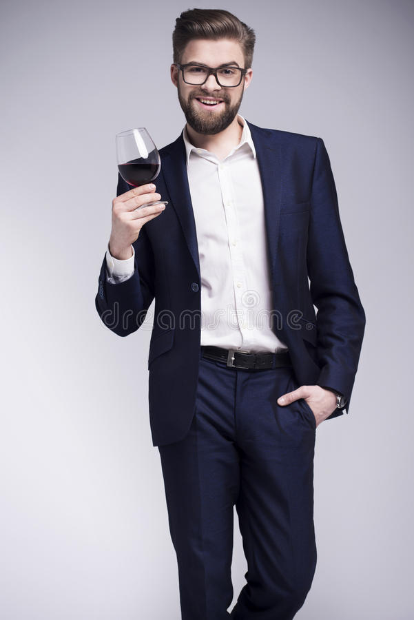 Handsome man with a beard holding a glass of wine in his hand royalty free stock photography