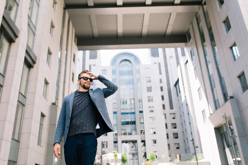 Handsome man with beard is posing to the camera on office building background. He wears T-shirt, jacket, jea stock image