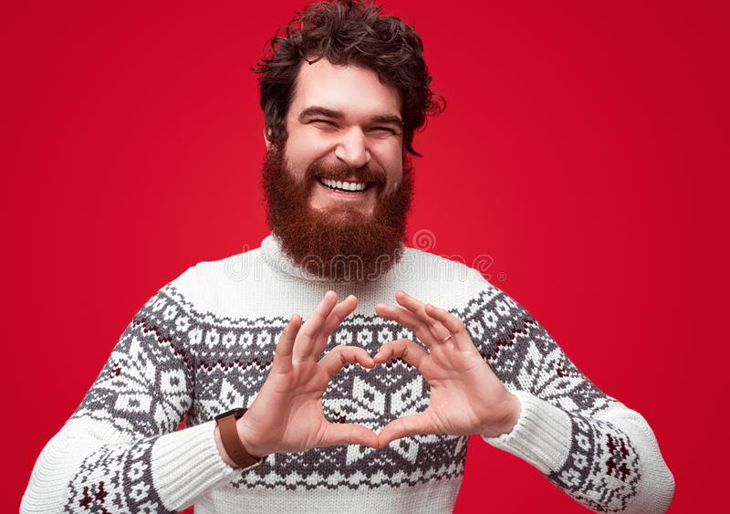 Handsome man with beard showing love and hear gesture stock images