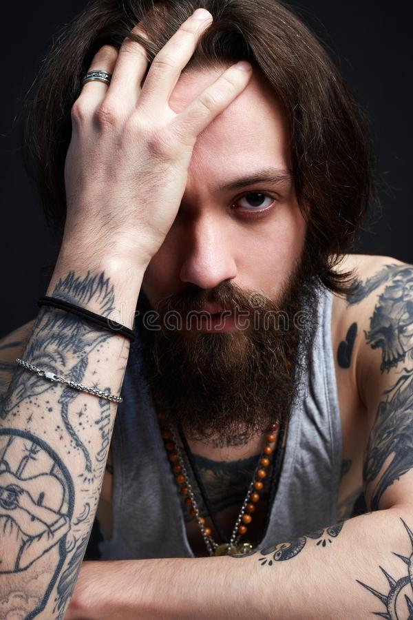 Handsome man with beard and tattoo. Bearded hipster boy. Emotion stock photography