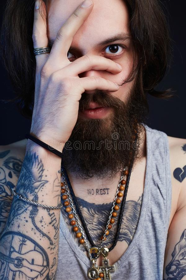 Portrait of handsome man with beard and tattoo. Handsome man with beard and tattoo. bearded hipster boy. emotion royalty free stock image