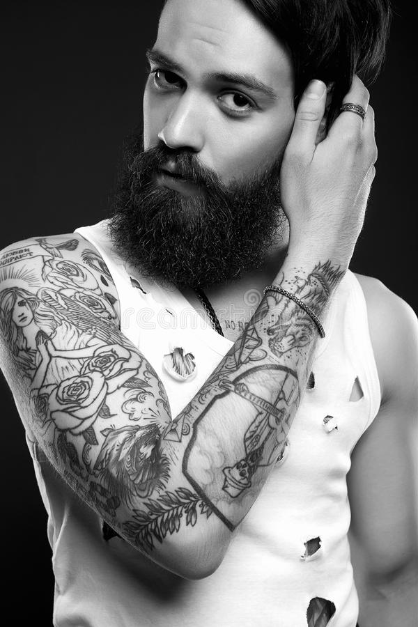 Handsome man with beard and tattoo. Black and white portrait of handsome man with beard and tattoo. bearded hipster boy in vintage torn dirty shirt stock photo