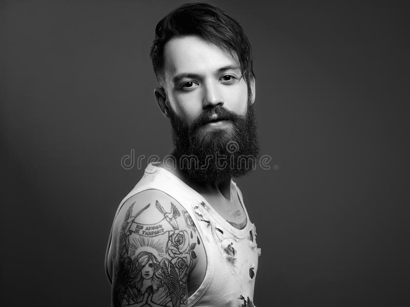 Handsome man with beard and tattoo. Black and white portrait of handsome man with beard and tattoo. bearded hipster boy in vintage torn dirty shirt royalty free stock image
