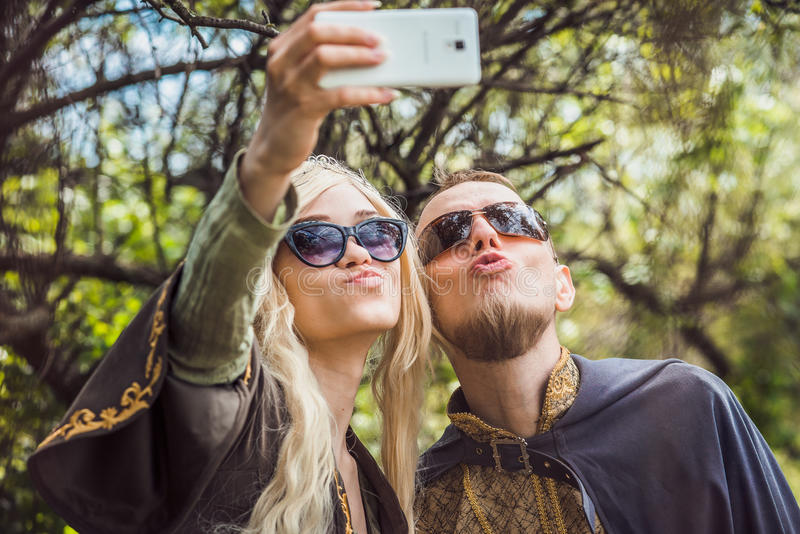Handsome man with beard and young pretty cheerful girl with glasses making selfie. stock images