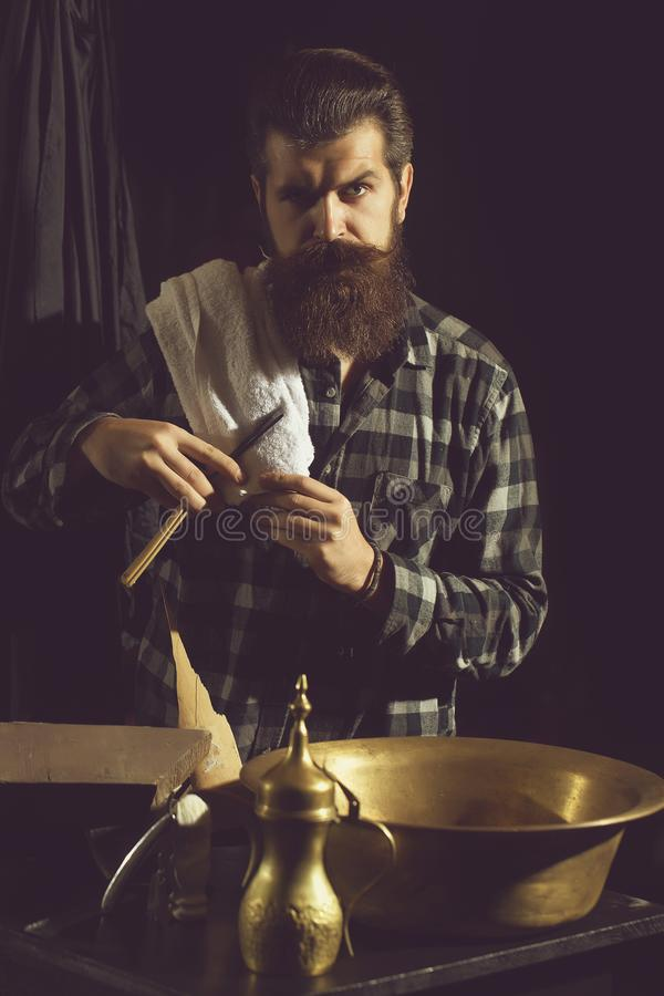 Bearded man shaves with razor stock image