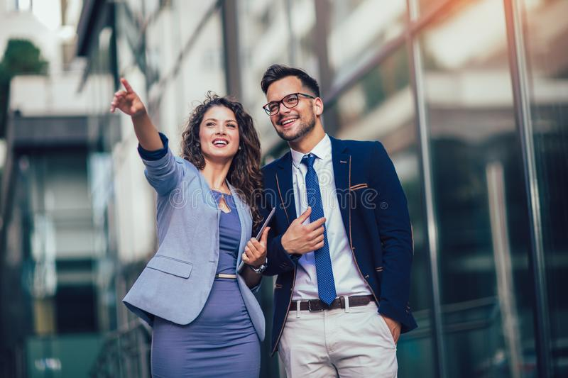 Young man and beautiful woman as business partners using digital tablet outdoor stock photos