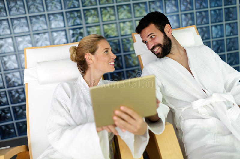 Handsome man and beautiful woman relaxing in spa. Handsome men and beautiful women spending time and relaxing in spa wearing bathrobes royalty free stock images