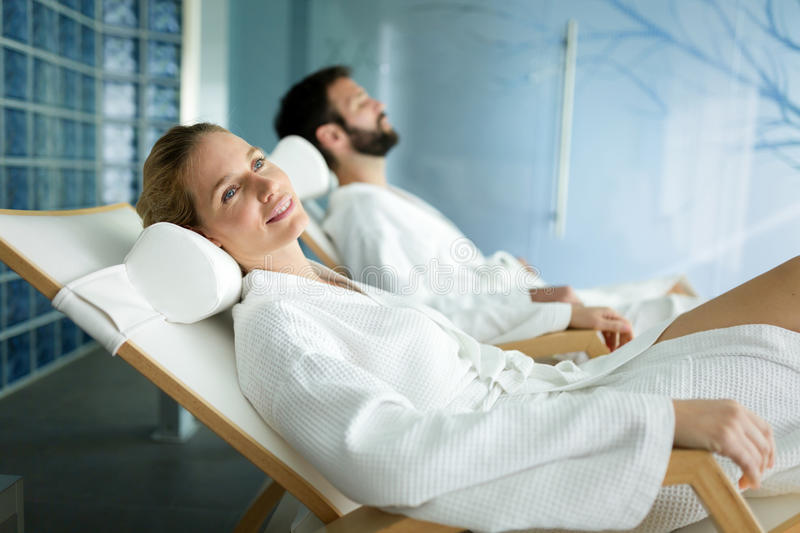 Handsome man and beautiful woman relaxing in spa. Handsome men and beautiful women spending time and relaxing in spa wearing bathrobes stock images