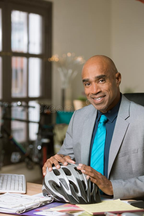Professional Man with Bicycle Helmet. Handsome man with a bicycle helmet seated at office desk stock photos
