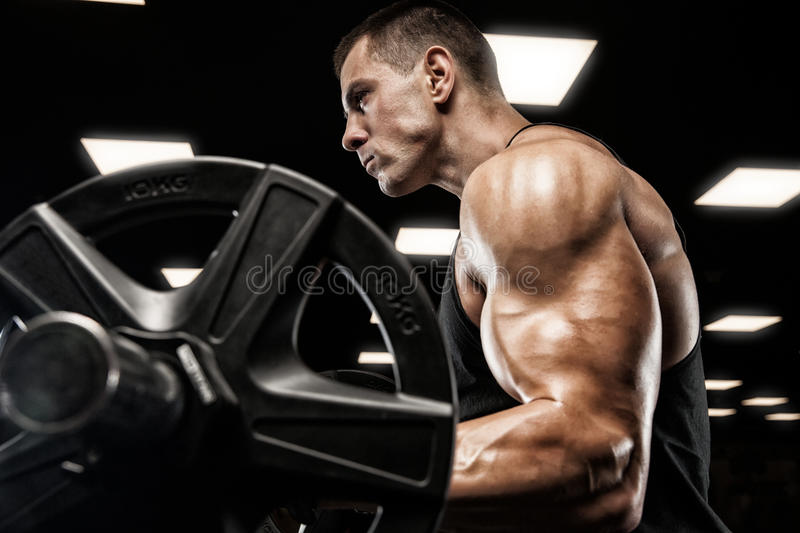 Handsome man with big muscles, posing at the camera in the gym royalty free stock photography