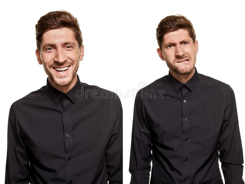 Handsome man in a black shirt makes faces, standing against a white background stock photography