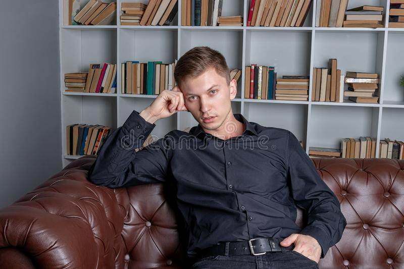 Handsome man in black shirt sitting on couch by bookshelves. Fashion concept stock photo