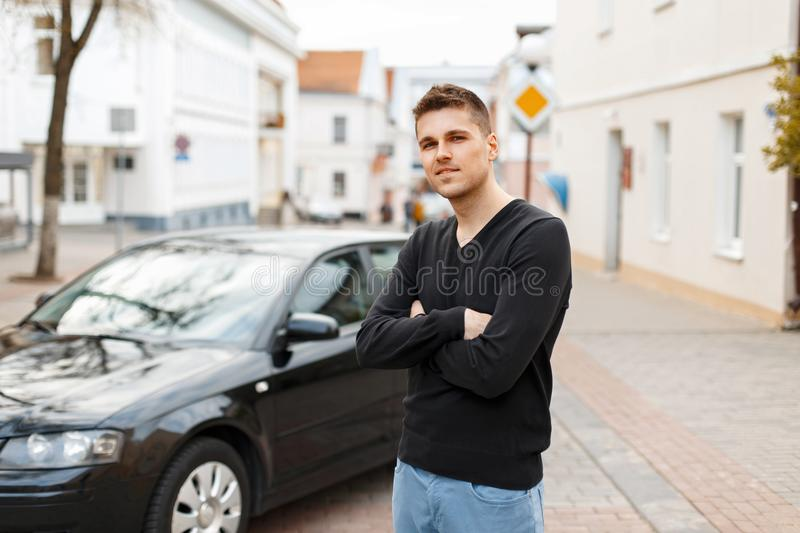 Handsome man in a black T-shirt near a car in the city stock photography