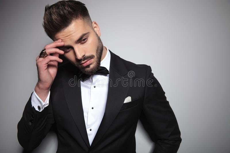 Handsome man in black tuxedo holding hand at forehead royalty free stock images