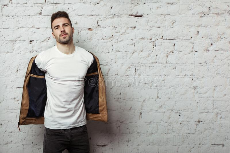 Handsome man in blank t-shirt taking off his leather jacket, white bricks wall background. Studio indoors stock image