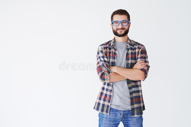Handsome man in blue glasses standing with arms folded royalty free stock photos
