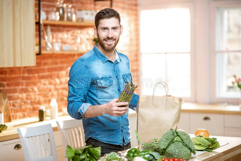 Man unpacking healthy food on the kitchen. Handsome man in blue shirt unpacking healthy food from the shopping bag on the kitchen stock photo