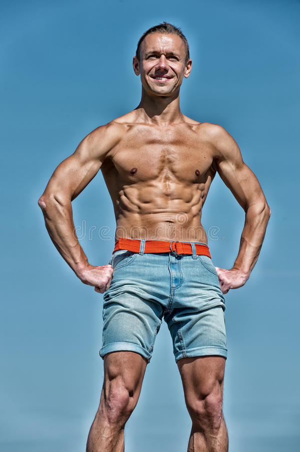 Handsome man bodybuilder with muscular body posing on blue sky. Handsome man with muscular body in shorts training sport, has smiling happy face, posing outdoor stock photos