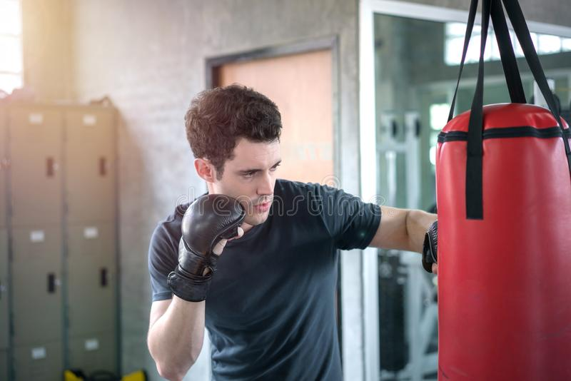 Handsome man in boxing gloves punching bags exercise in fitness gym royalty free stock photos