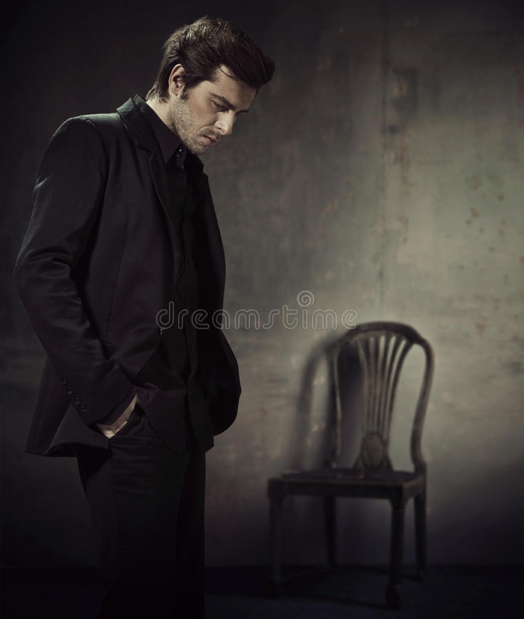 Handsome man in a business suit on a dark background stock image