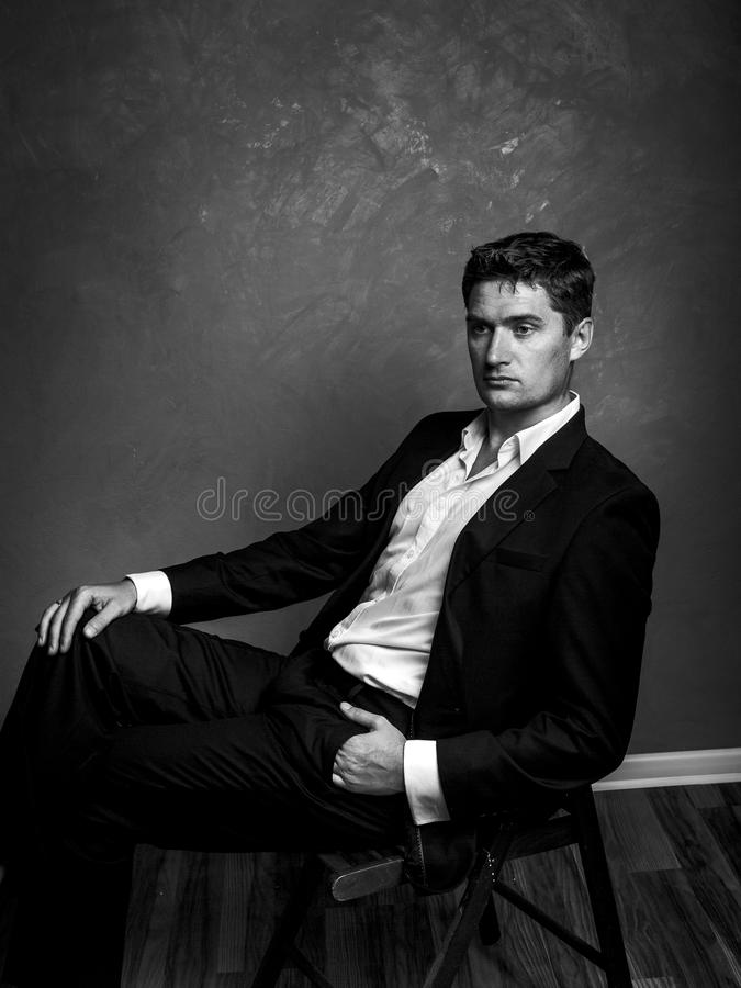 Handsome man in a business suit sits on a chair and looks away, style fashion black and white portrait stock image