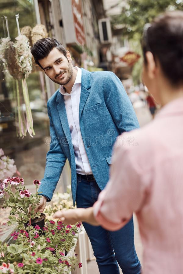 Handsome man buying flowers at florist. Handsome young men buying flowers at florist, smiling stock images