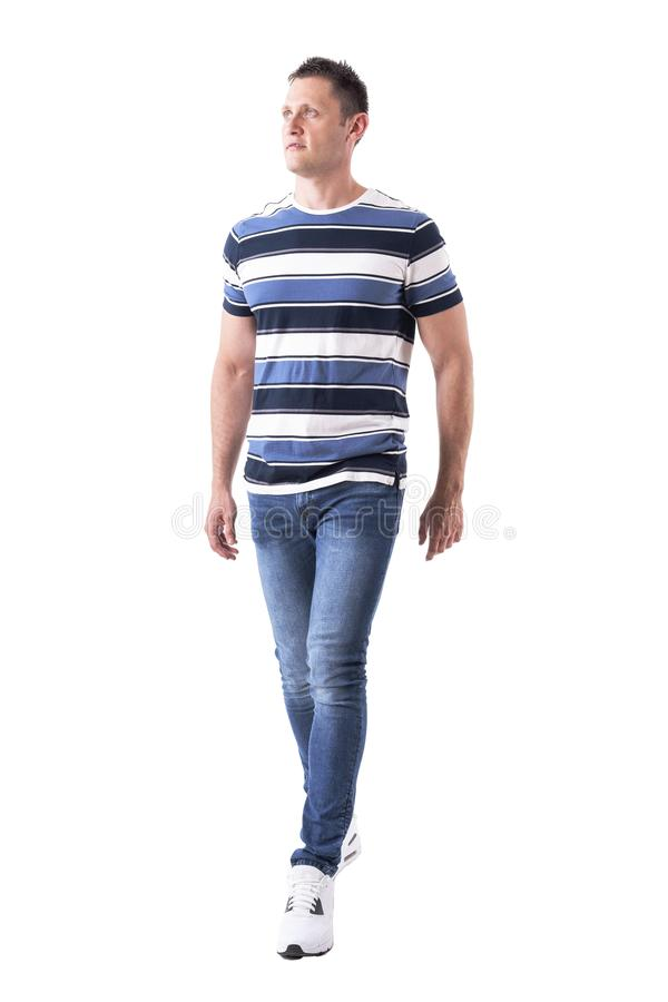 Handsome man in casual clothes approaching and looking up wearing jeans. Full body isolated on white background royalty free stock photos