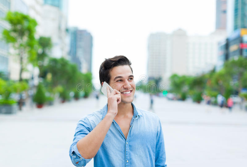 Handsome man cell phone call smile outdoor city stock photography