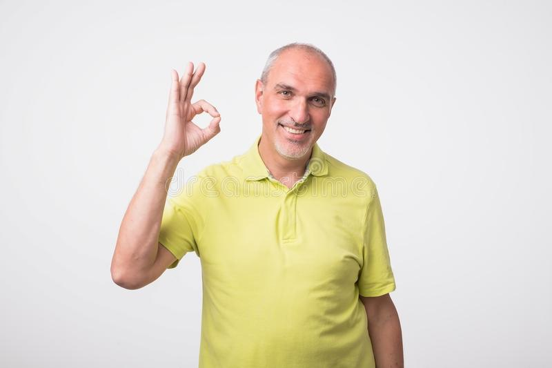 A handsome man in checkered shirt isolated on gray background showing ok sign. A handsome mature man in yellow shirt showing ok sign. Concept of well done work stock photos