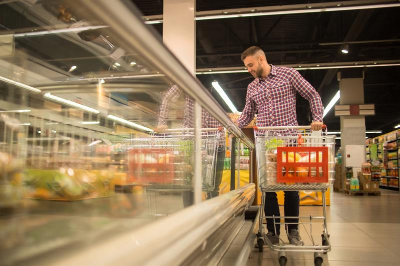 Handsome Man Choosing Food in Supermarket. Full length portrait of handsome young man with shopping cart choosing groceries in supermarket looking at frozen stock photo